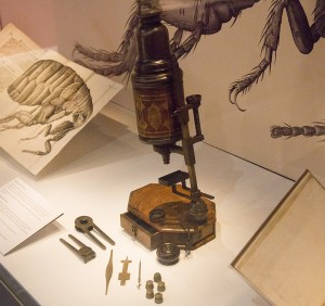 A picture of the microscope on loan to the National Library of Wales inside the exhibitions display case, with an image from Hooke's Micrographia to the right.