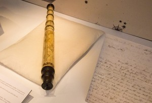 The telescope sent on loan to the exhibition rests in the centre of the case on a pillow, with a letter displayed to its right.