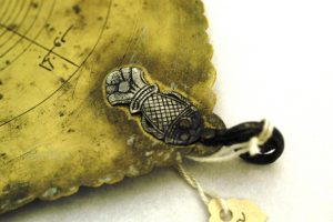 A close-up of the delicate, coin-sized fish attached to the astrolabe.