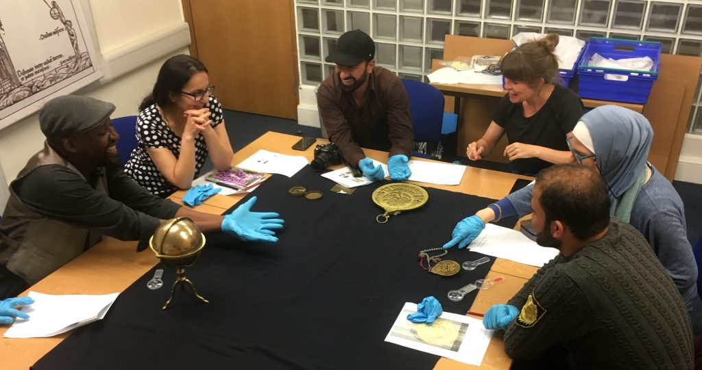 Six people from the Multaka-Oxford team sitting around a table discussing astronomical instruments. In front of them are two astrolabes of different sizes, and a globe sitting in a brass mount.