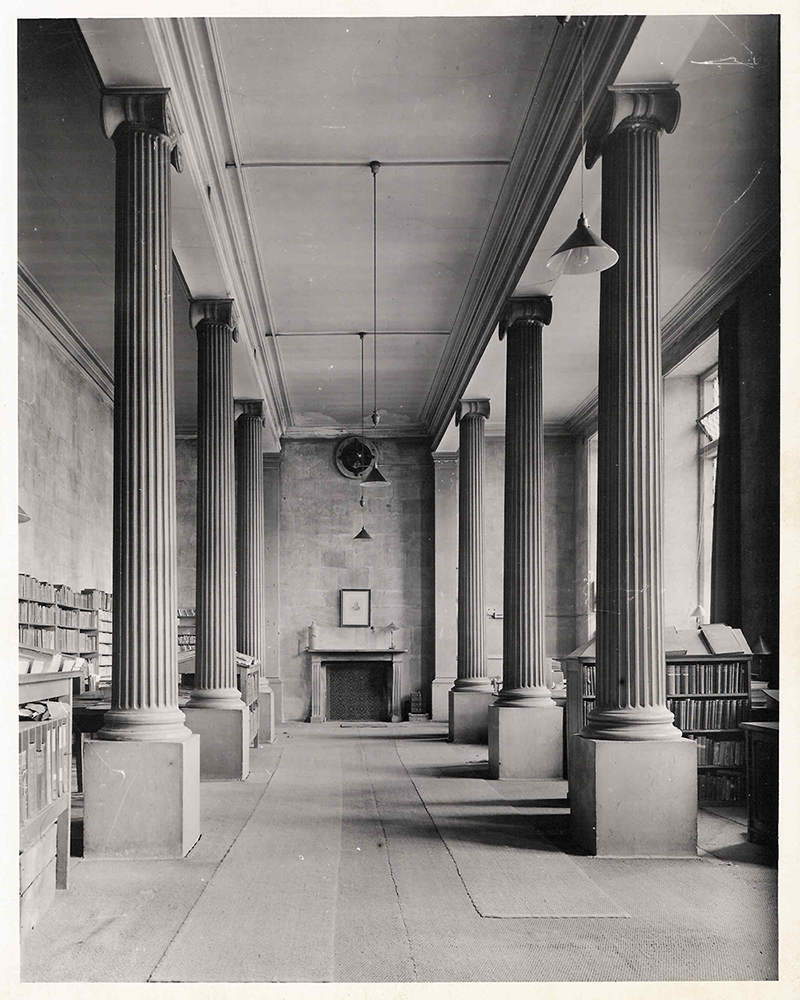 the main floor of the building, it is mostly empty with desks running down the right side of the room and shelves on the left.]