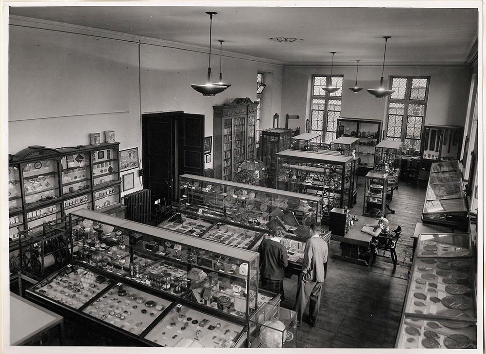 the top floor of the building, showing wooden exhibition cases of various sizes filled with objects. A woman is sitting at a desk reading, and a man and a woman are leaning over one of the cases.]
