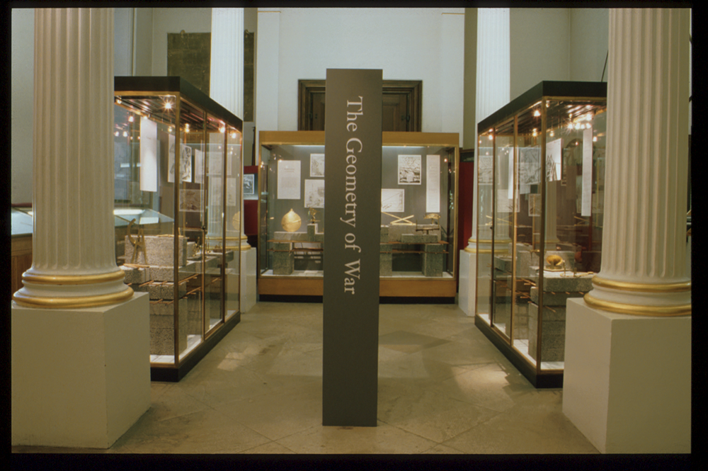 a photograph of the exhibition Geometry of War. A large pillar stands in the middle with the exhibition title on it. To either side, and behind pillars, are the first two exhibition cases