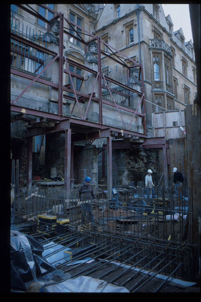 The outside of the Museum during extensive renovations in 1999. The ground in front of the Museum has been dug up, and the photo is taken from the hole while looking up to the Museum. The front wall is held up on metal stilts.