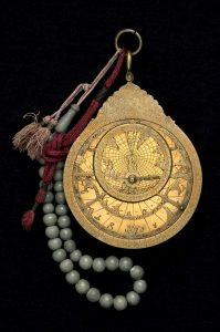 Astrolabe with green prayer beads and red cloth handle.