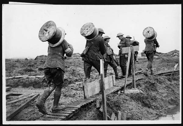 IWM Q 6050 Battle of Poelcappelle. Royal Engineers taking drums of telephone wire along a duckboard path up to the front between Pilckem and Langemarck, 10 October 1917.