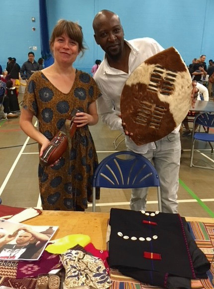 Rachel and Thabo standing in a large sports hall behind a table of Museum handling objects. Thabo is holding a shield and Rachel is holding a type of flask.