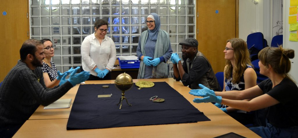 Group of volunteers sitting and standing around a table looking at brass astronomical instruments.