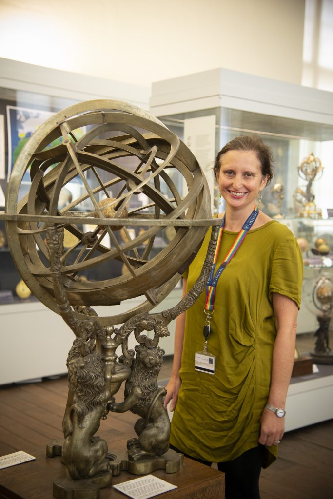 Helen Pooley standing behind the armillary sphere - an interlocking set of rings balancing on top of three lions. The armillary sphere is the same height as Helen.