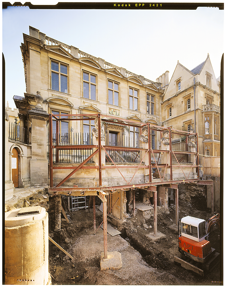 The outside of the Museum during extensive renovations in 1999. The ground in front of the Museum has been dug up to improve the foundations, and the photo is taken from the hole while looking up to the Museum. The front wall is held up on metal stilts. The image is in bright colour